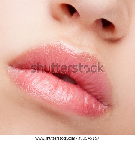 Close-up beauty shot of female full lips with healthy skin and rose color lips