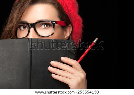 Close up Beauty Stylish College Girl with Expressive Eyes in Trendy Eyeglasses Covering her Face with Black Notebook While Holding a Pencil. Isolated on Black Background with Copy Space for Text - stock photo
