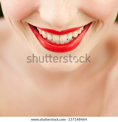 Close up beauty view of an attractive young woman's smiling mouth wearing bright red lipstick cosmetics on her lips, smiling. - stock photo
