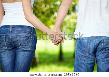 Close up behind keeping hands enamoured, walking in park - stock photo