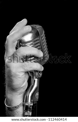 Close up black and white image of a vintage microphone on a stand being cupped by a male hand