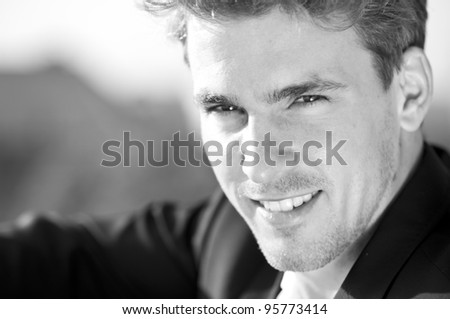 Close-up black and white portrait of beautiful young man turning toward viewer - stock photo