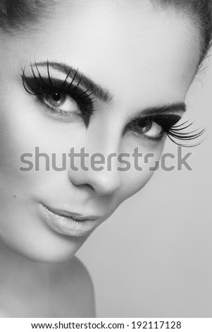 Close-up black and white portrait of young beautiful woman with stylish make-up and huge false eyelashes - stock photo
