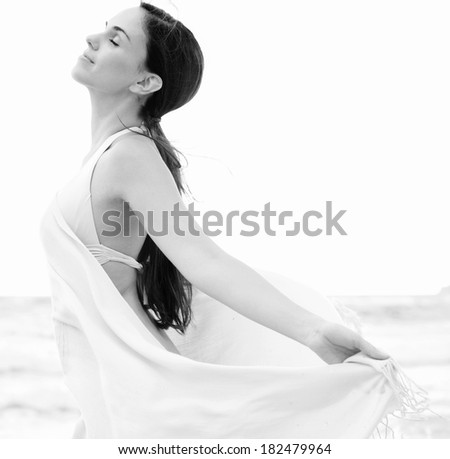 Close up black and white side portrait of a beautiful woman relaxing on a beach on holiday holding a pink fabric sarong around her body and floating in the breeze, breathing fresh air, lifestyle. - stock photo
