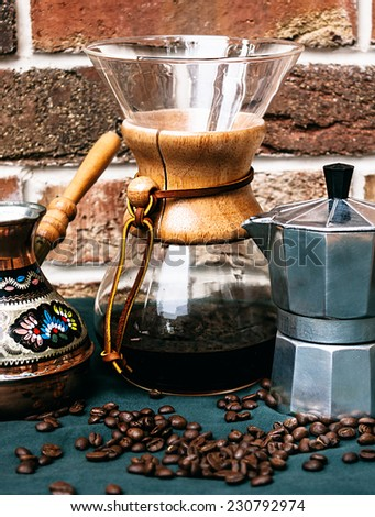 Close up Black Coffee Maker and Containers on Green Table with Coffee Beans - stock photo