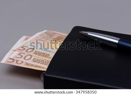Close up black daily planner with luxury ball pen and some euro banknotes on grey background. - stock photo