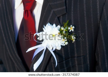 close-up black jacket groom on their wedding day with a red tie and lapel buttonhole