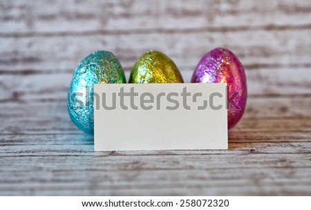 Close up Blank White Greeting Card In Front of Three Easter Chocolate Eggs on Top of a Wooden Table with Blurry Background. - stock photo