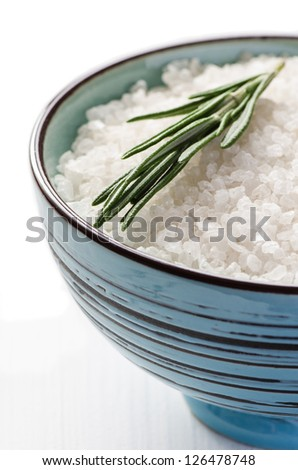Close up blue clay bowl with sea salt and rosmary on white wooden table