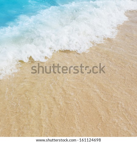 Close up blue sea water waves with bubbles on sand beach - stock photo