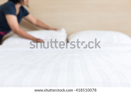 Close up blur woman set up white bed sheet in hotel room - stock photo