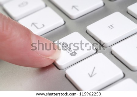 Close up blurred view of female hand touching computer keyboard-delete - stock photo