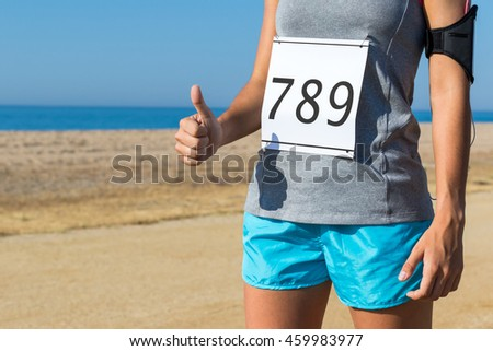 Close up body part of female athlete with race start number doing thumbs up outdoors.