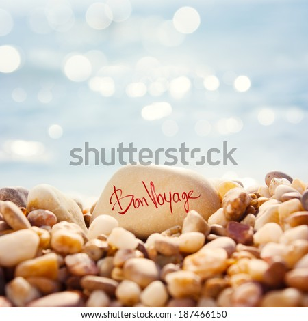 """Close Up """"Bon Voyage"""" Text Written on the Stone at the Beach. Sea Pebble with Shallow Depth of Field and Beautiful Bokeh. Toned Photo. Summer Vacation Concept. - stock photo"""