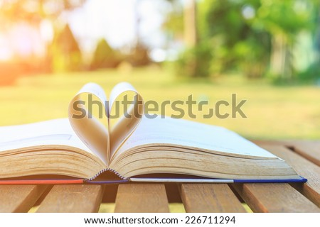 Close up book on table in the garden - stock photo