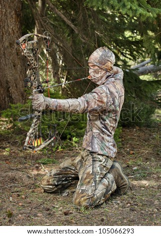 close-up bow hunter dressed in camouflage pulling bow back in woods