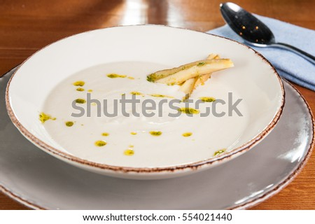 Close up bowl of cream celery soup on the served table. Selective focus