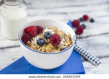 close up bowl of muesli breakfast and raspberries and blueberries on bright blue napkin and bottle of milk - stock photo