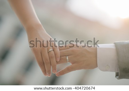 close up bride groom holding hand with sunset (selective focus) - stock photo