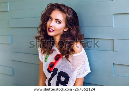 Close up bright fashion portrait of pretty young teen hipster woman with bright make up and stunning curled fluffy brunette hairs, wearing sportive outfit and neon sunglasses, urban background. - stock photo