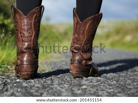 Close up brown leather boots standing on road in countryside