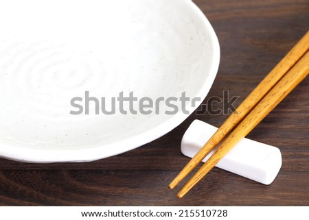 Close - up brown wooden chopsticks on table wood background   - stock photo