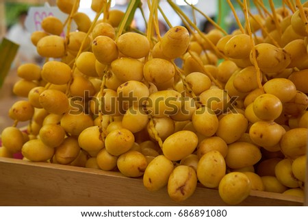 Close up Bunch of Yellow Raw Fresh Organic Dates in Wooden Box