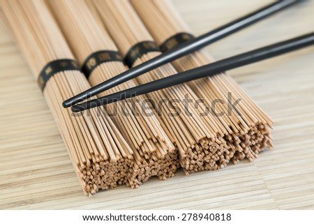 close-up bundles of soba noodles and black chopsticks - stock photo