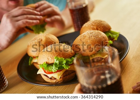 Close up burgers and cola on the table served for party - stock photo