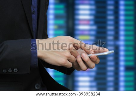 close up business man checking market price by smart phone mobile device over blurred stock trade board chart.economics/economy concept.investor using wifi technology for  follow information commerce. - stock photo