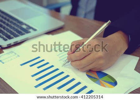 close up business man hand with pen writing on statistics paperwork concept:vintage filter effect tone color. - stock photo