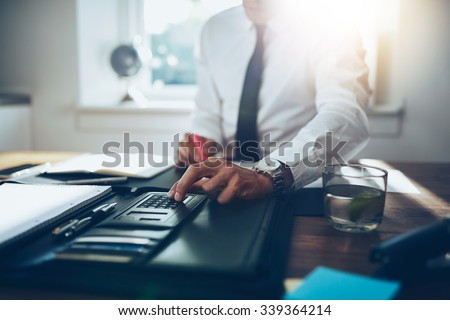 close up, business man or lawyer accountant working on accounts using a calculator and writing on documents - stock photo