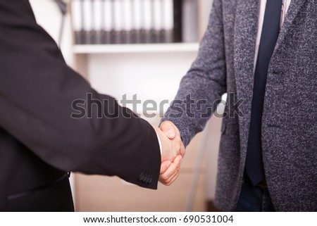 Close up Business partners shaking hands in the office. Two businessman in formal suits shaking hands in corporate office eviroment