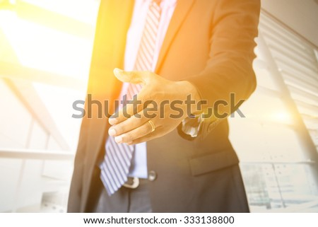 Close up business people hand offering handshake, golden sunlight from background, sunrise or sunset business. - stock photo