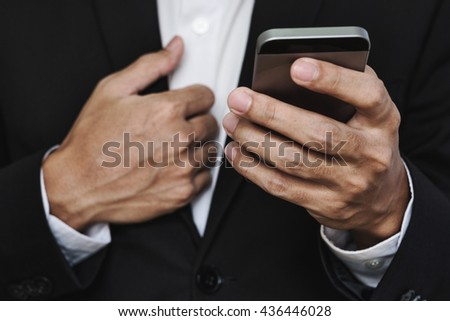 Close-up businessman hand using smart phone, with another hand holding suit collar