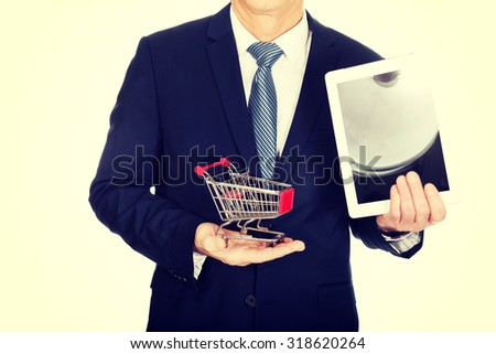 Close up businessman holding shopping cart and tablet.