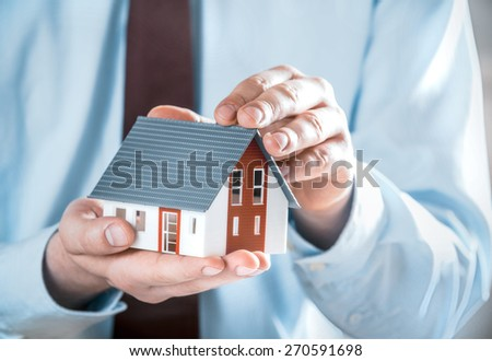 Close up Businessman in Business Suit Holding a Cute Miniature House Model Using his Both Hands. - stock photo