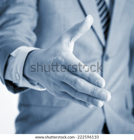 Close up businessman offer hand shake, in blue toned effect. - stock photo