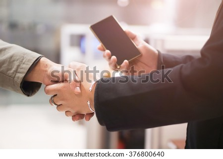 Close up  businessman using smartphone. Business concept and shake hands - stock photo