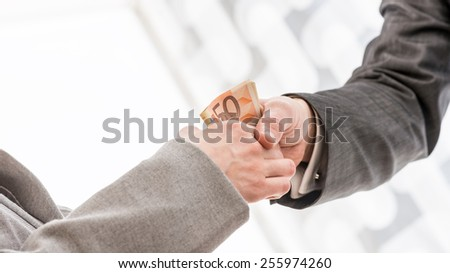 Close up Businessman with Money Handshaking with his Business Partner Inside the Office. - stock photo