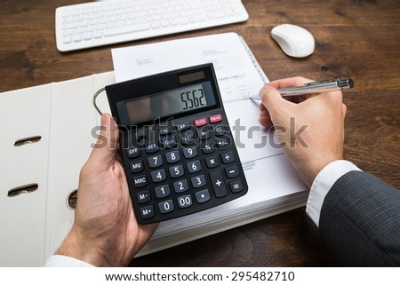 Close-up Businessperson Hand Calculating Financial Result With Calculator In Office - stock photo