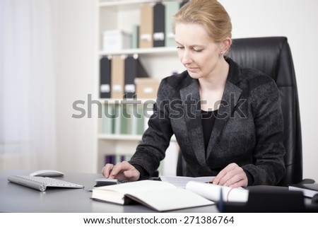 Close up Businesswoman in Black Fashion Sitting at her Table While Calculating Sales Seriously. - stock photo
