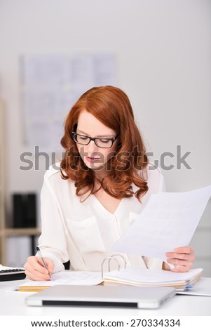 Close up Busy Young Office Woman Sitting at her Worktable, Writing Document Seriously While Holding Other Papers. - stock photo