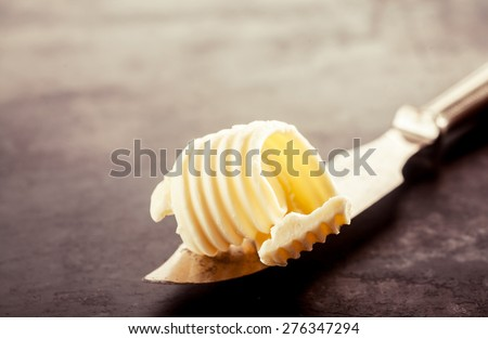 Close up Butter on a Knife for Bread Filling, Placed on Top of a Vintage Wooden Table - stock photo