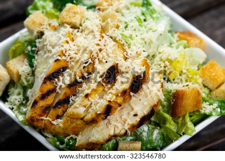 Close Up Caesar salad with chicken and lettuce on wooden table. - stock photo