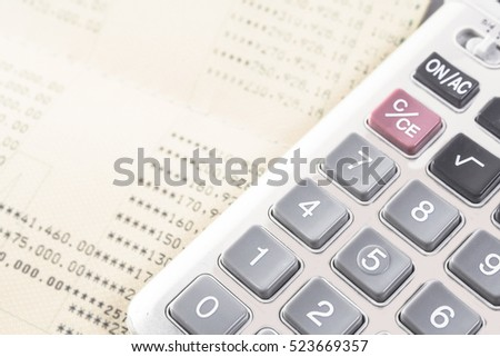 close up calculator with blurred book bank statement  background