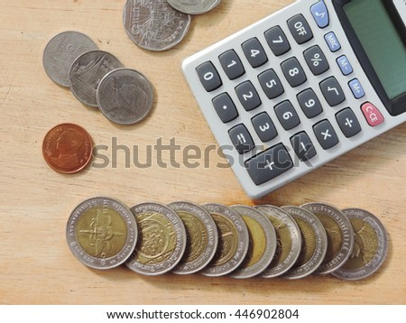 close-up calculator with coins,different THB coins on the background of wood,select focus,Money concept.            - stock photo