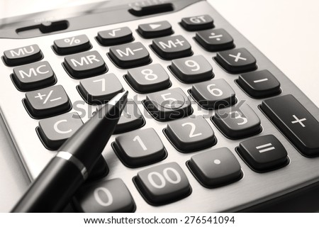 close up calculator with pen on white paper, sepia tone - stock photo