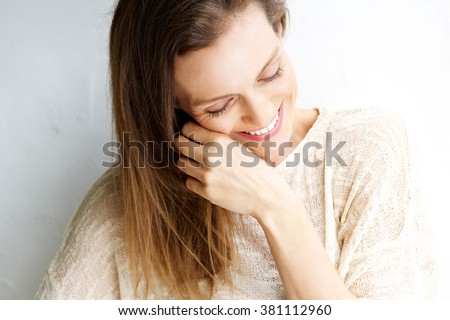 Close up candid portrait of a woman laughing against white background - stock photo