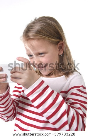 close up candid portrait of beautiful female child with blond hair and blue eyes using mobile phone playing game excited isolated on white background in children internet gaming addiction concept - stock photo